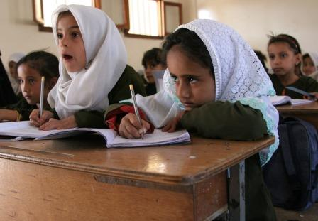 A group of girls in another country sitting at desks with pencils and learning in school.