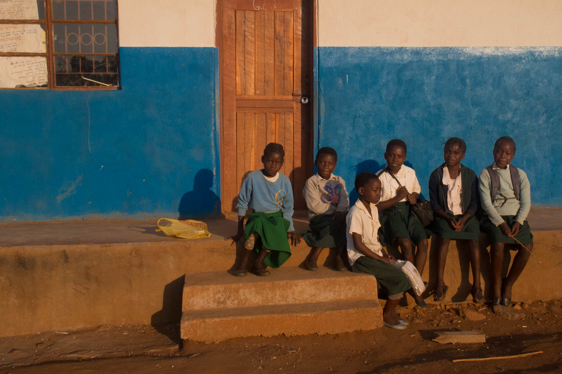 picture credit Albert Tholen children in Zambia sit outside a building