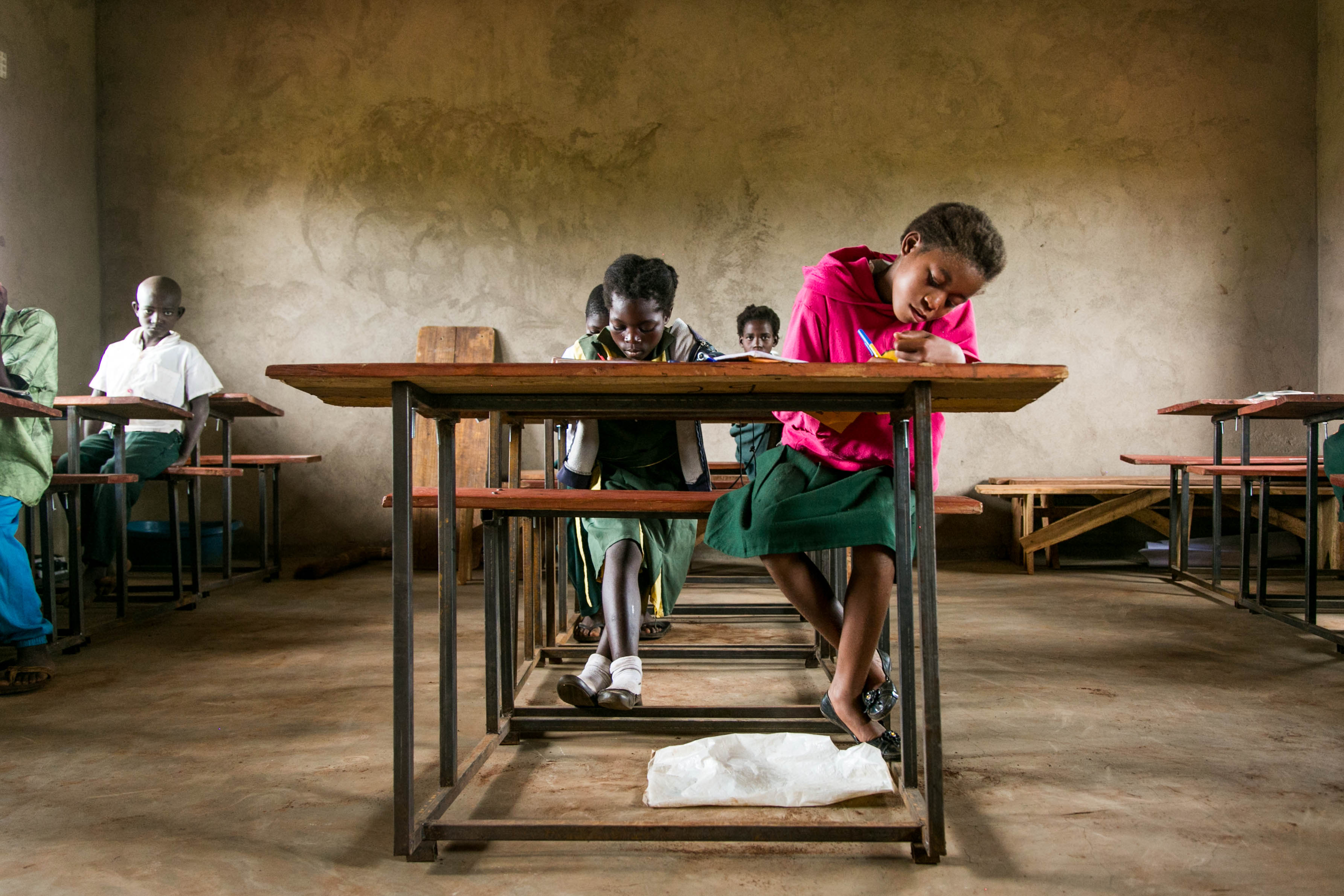 students hard at work at their desks in a Zambian classroom by Kristyn Ulanday
