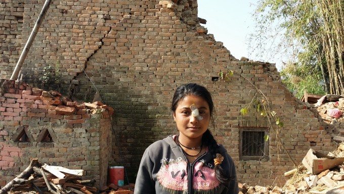 Scholar Anjana Poudel stands in front of her destroyed home. Her quick thinking, which made her jump out of the second story of the house saved her life with minimal injuries.