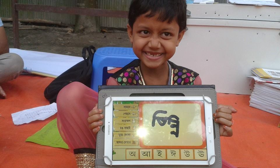 Young girl smiling with a tablet she uses to help with literacy