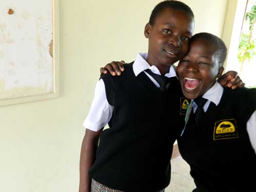 Two girls smile for the camera in their school uniforms