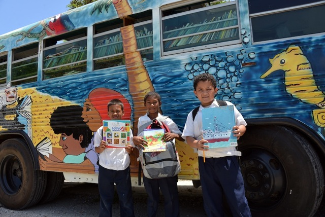 Roatan Bookmobile with three boys standing outside it with books