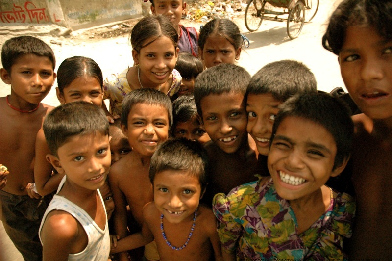 This is a group of young boys and girls grouped together and smiling while looking at the camera in Southeast Asia.