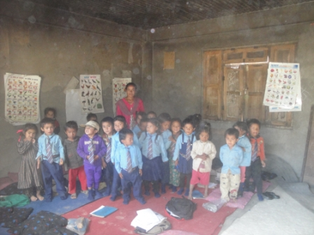 Pre-primary students standing with their teacher in their classroom