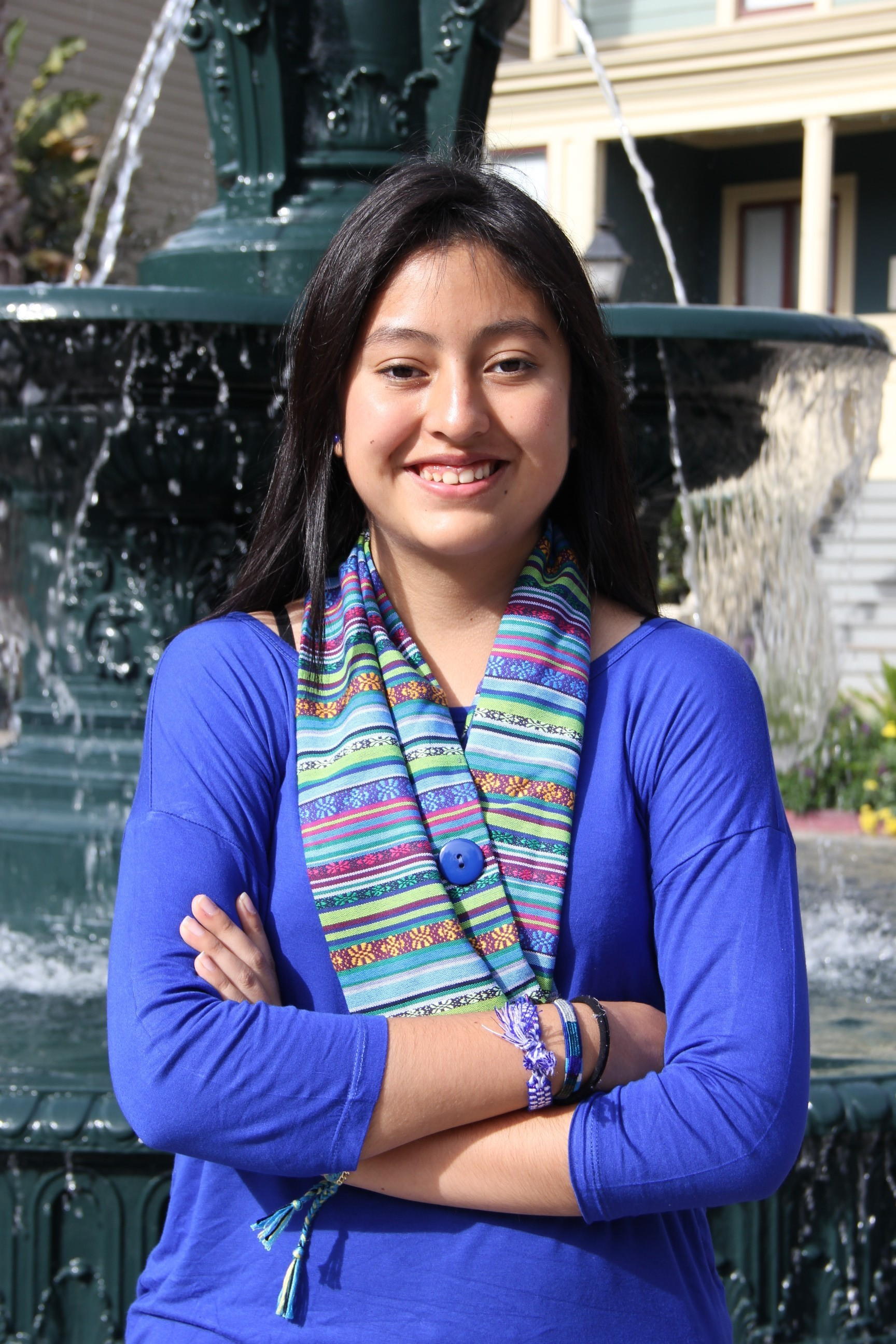 Alejandra, a Rise Up girl leader poses with her arms crossed and smiles outside a building with a fountain in front of it.