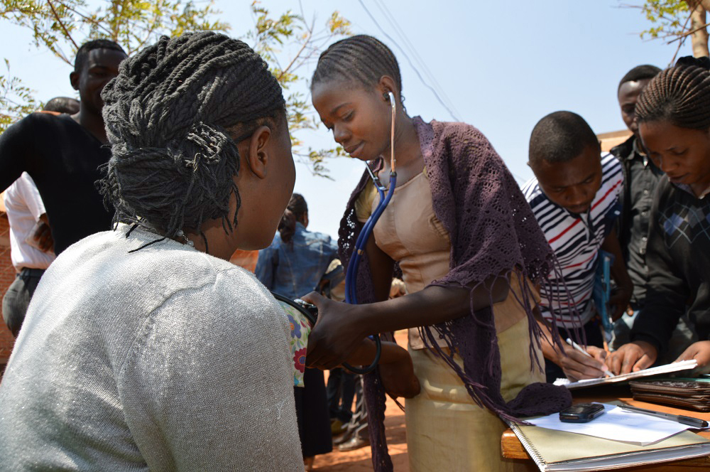 Participants in a community health course measure blood pressure at Dzaleka Refugee Camp, Malawi. (Gushwell F. Brooks — Jesuit Refugee Service)