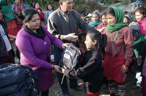 ETC-Nepal Director Mira Rana and Education Director Laxmi Basukala present a child with her new backpack full of useful supplies