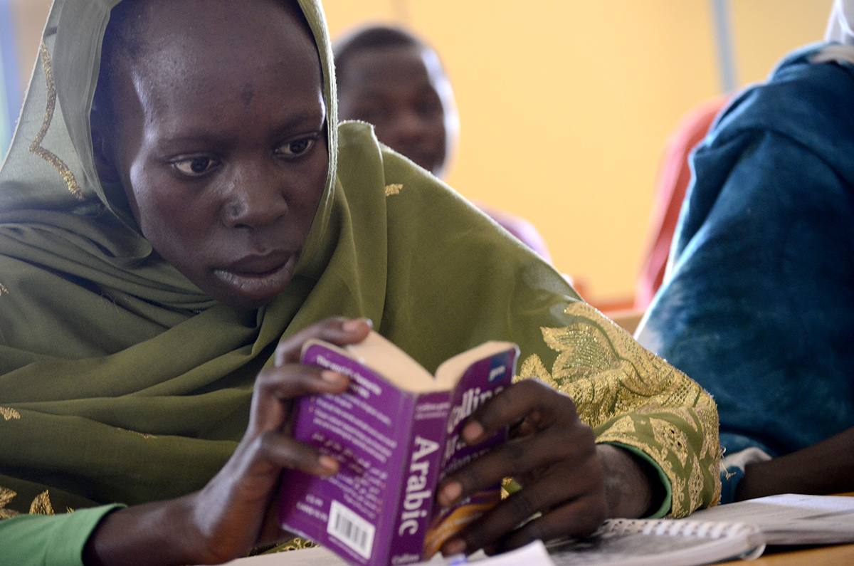 A refugee from the Darfur region of Sudan consults her dictionary during an English class in the JCHEM program at Djabal refugee camp in Chad. (Christian Fuchs — Jesuit Refugee Service/USA)
