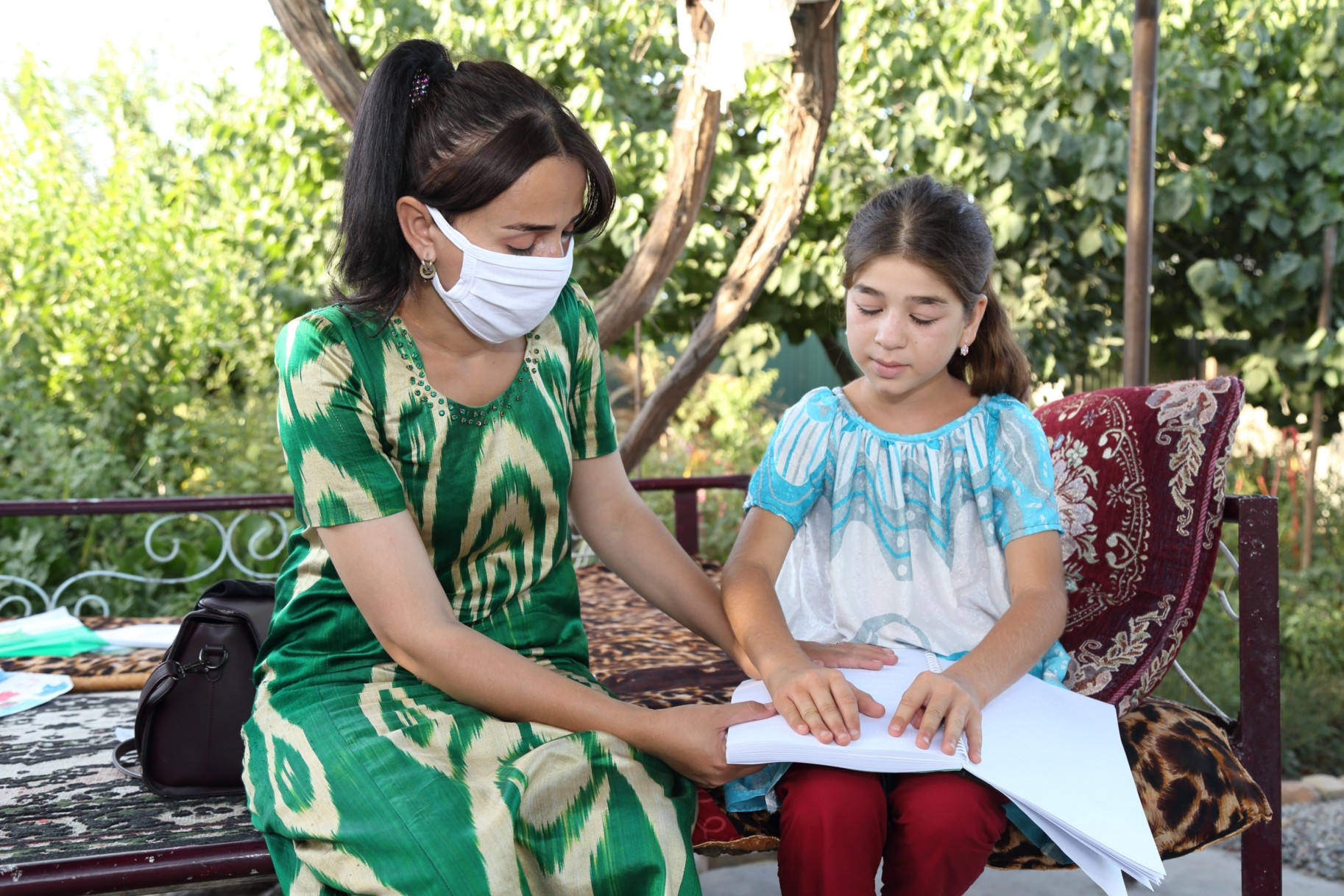 Roziya Boboeva, a teacher in Tajikistan, visits the homes of four of her students who have low vision — including Manija Sharipova — with USAID-donated Braille books and books with large print. / Photograph by Rustam Mailov for USAID