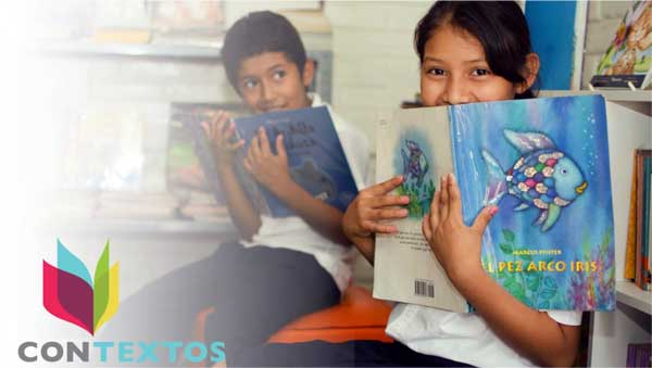 two students hold books in a Contextos library