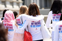 Photo from Girl Up shows a group of happy girls with their arms around each other walking. They are wearing empowering girls shirts.