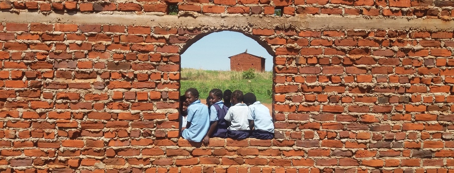 Photo Credit: Impact Network, the photo shows a group of children sitting in a glassless window in a brick building, joyously.