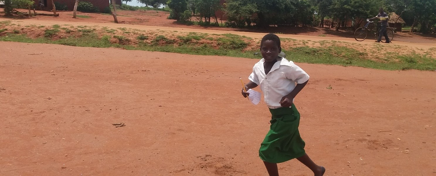 Photo credit to Impact Network. The photo shows a young girl running joyously across an open area in Zambia