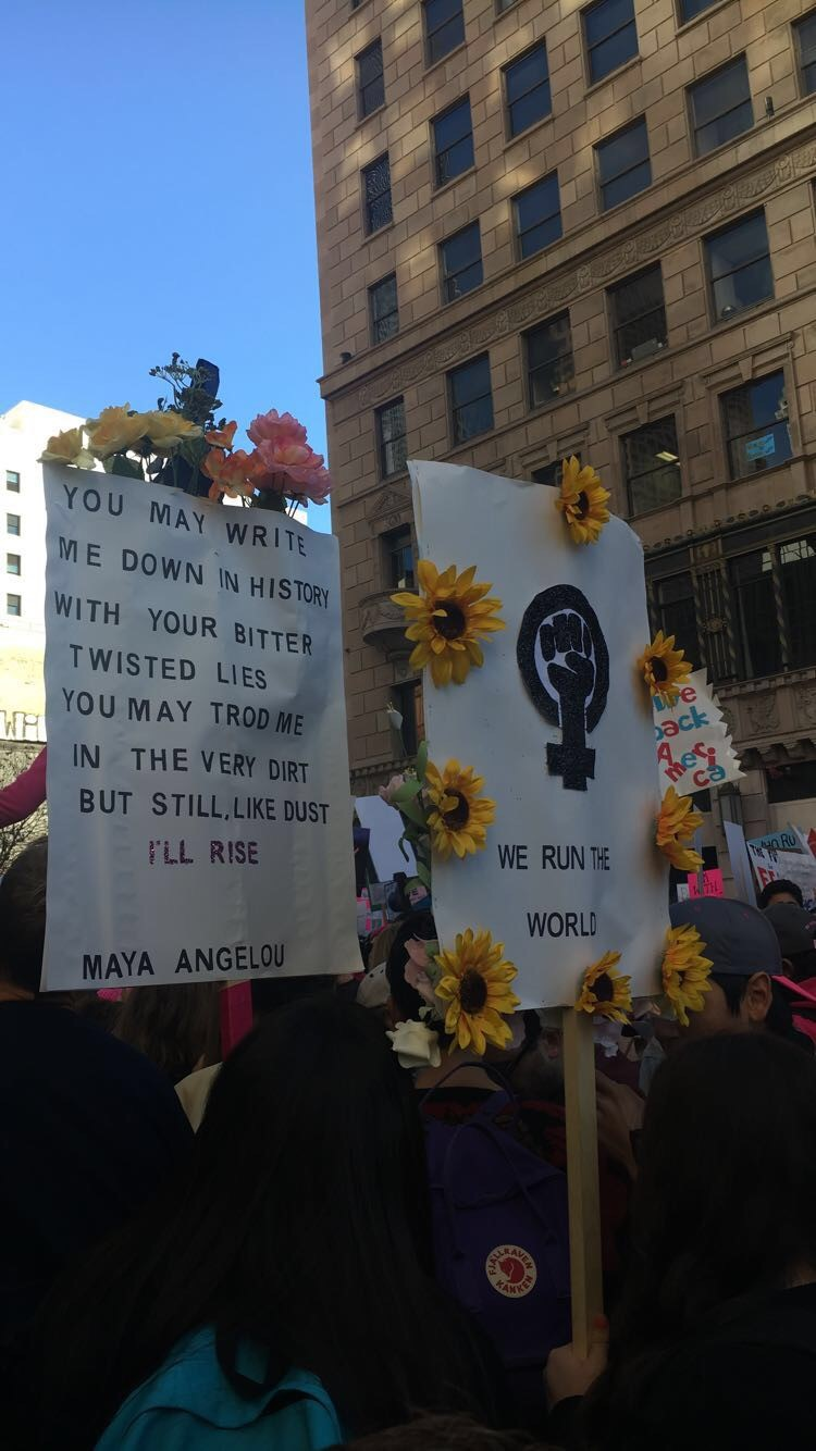 A photo from a woman's empowerment march that has an inspiring quote from Maya Angelou and other empowering women slogans.