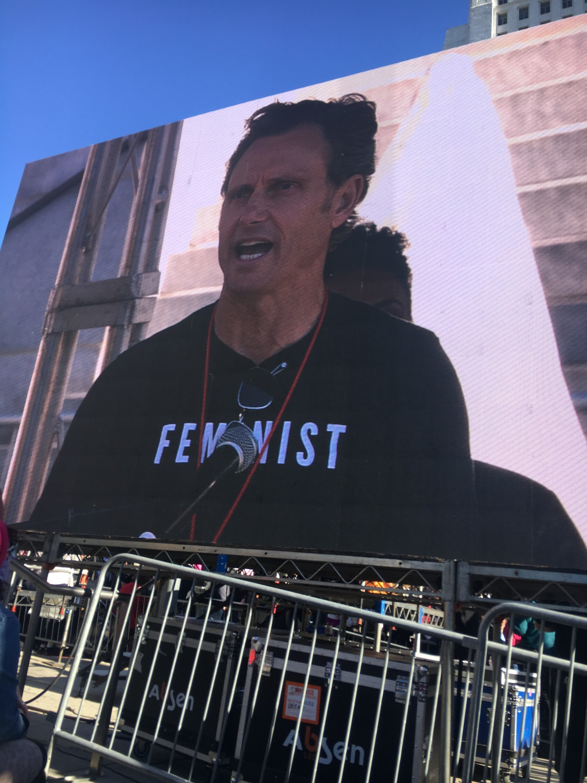 Photo from the woman's march that has a picture of a male participant wearing a t-shirt that says