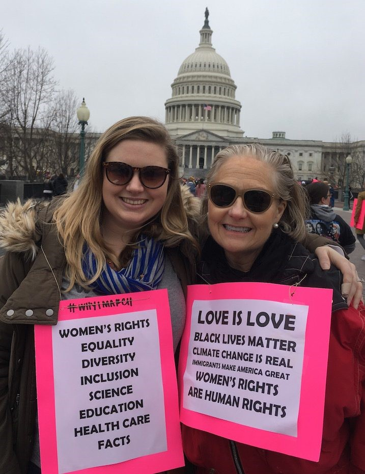 A photo from the women's march. Two women are standing in front of Capitol Hill with signs that promote women's rights, equality, inclusion and love is love.