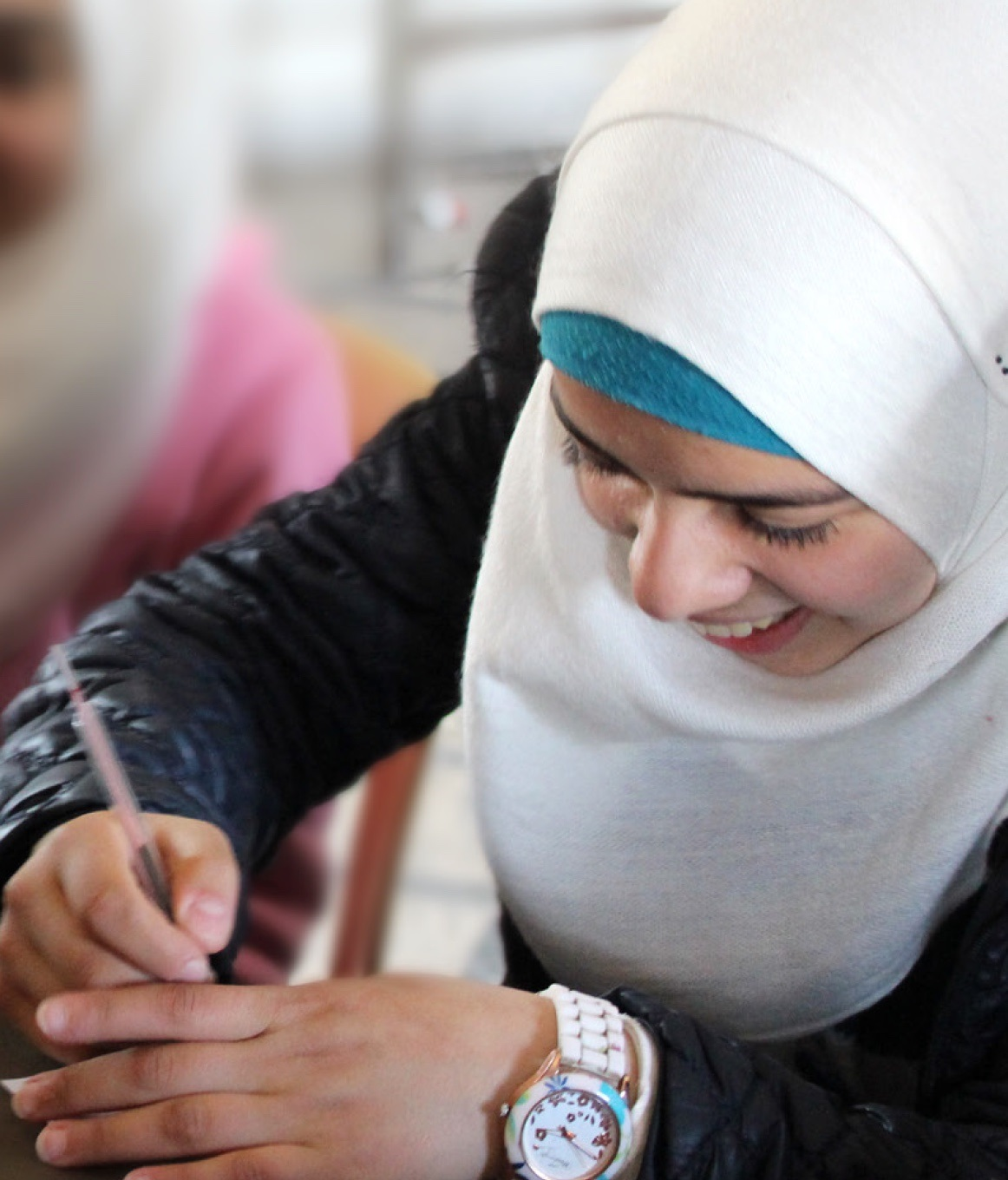 Photo of Rama a thirteen-year-old girl, from Homs, Syria who is enrolled in a Jesuit Refugee Service (JRS) center for children. She is sitting at a school desk, writing.