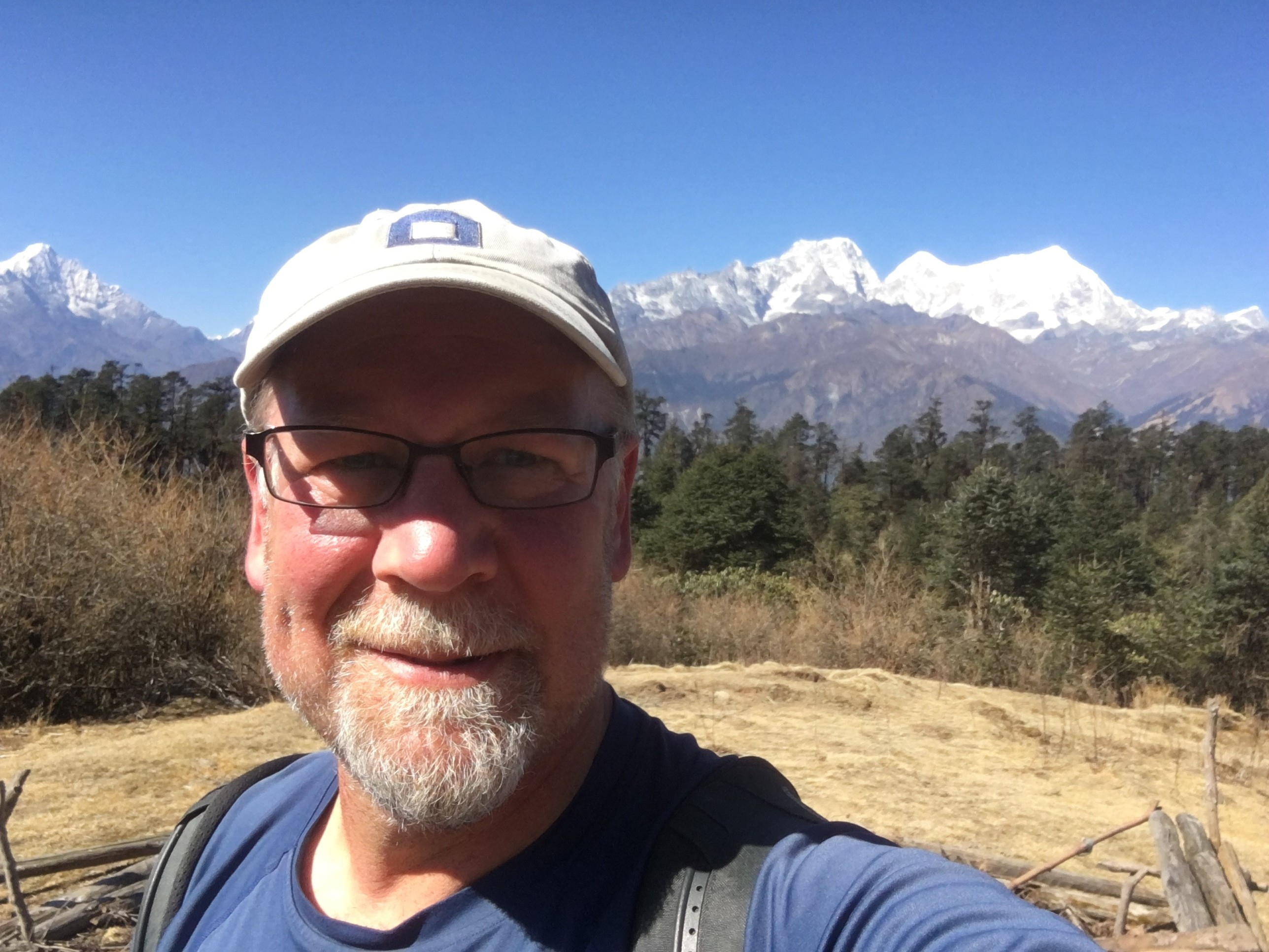 Photo of Edge of Seven, Executive Director Peter Mason. He is standing in front of a mountain, smiling in nature.
