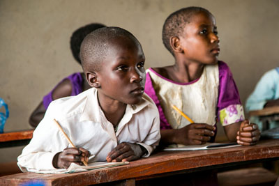 Two boys listen in class at their desk