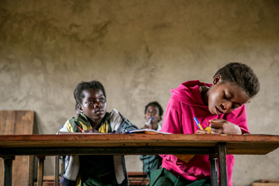 Two girls take notes at their desk in a classroom