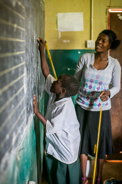 A teacher helps a student at the chalkboard
